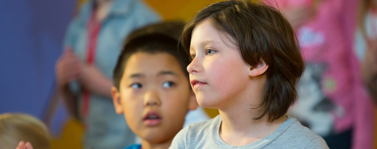 An elementary girl has a serious expression during a lesson on grief.