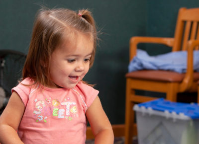 A preschool girl is happily smiling as she participates in the sharing song.
