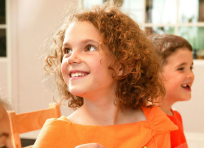 A young girl is sitting at a table with two friends. She's looking up and over her shoulder and smiling at her teacher.