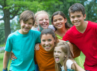 A group of five older elementary kids hug their small group leader.