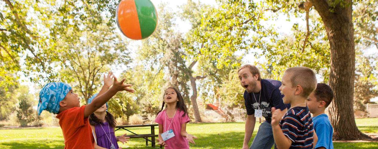A group of preschoolers are playing an icebreaker outside with an inflatable beach ball.