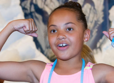 A preteen girl flexes her muscles during a strongman relay game.