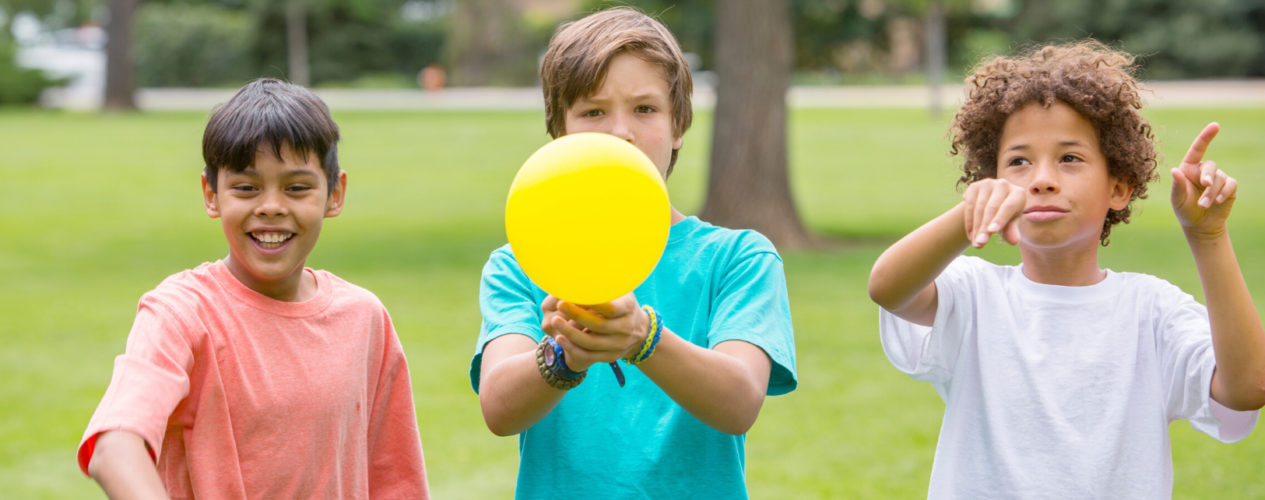 Three preteen boys stand in a line. The middle boy is holding a balloon.