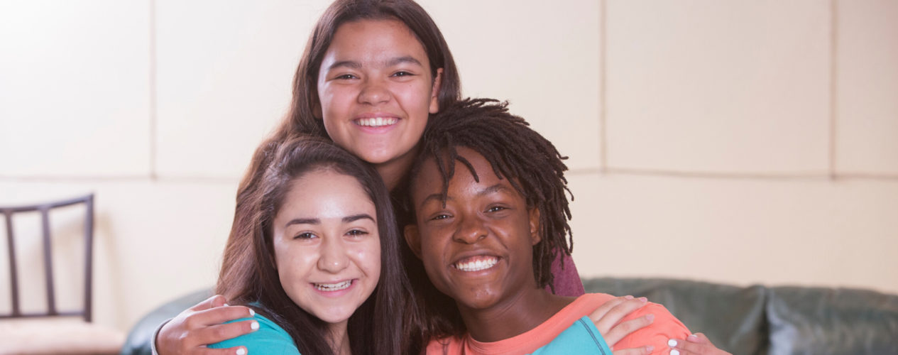 A group of three preteen girls are smiling as they participate in a lesson on God and Abraham.