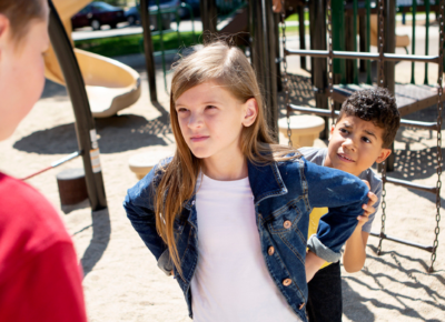 Girl in jean jacket standing with her hands on her hips as a boy stands scared behind her. She's standing up to a bigger boy facing the two of them.