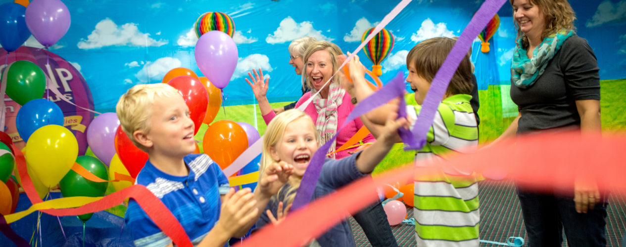 A group of children excitedly celebrate as streamers and balloons fall from the sky.