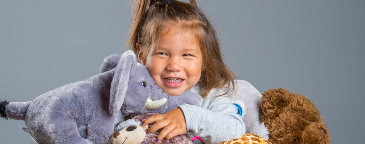 A toddler girl has an arm full of stuffed animals.