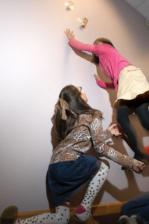 A preteen girl helps try to life another preteen girl up to grab a chocolate bar that's taped to the wall.