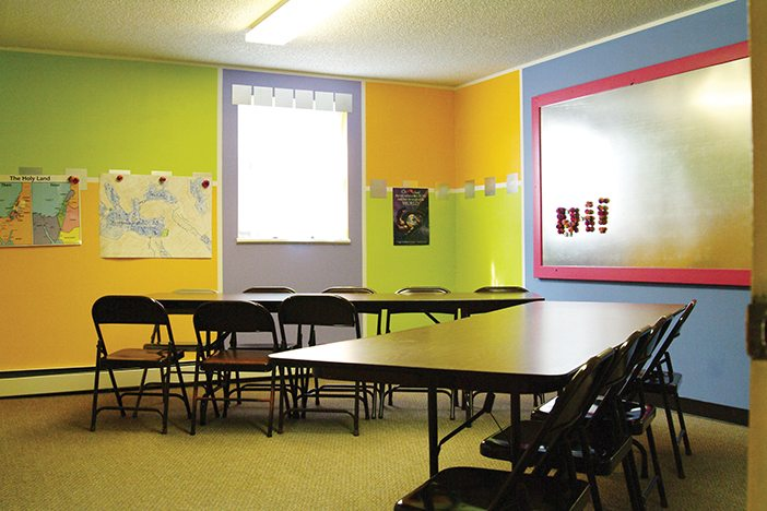 A classroom with two sets of tables and chairs. The walls are painted vibrant shades of green, orange, and blue. There is a tin magnet board on one wall, and posters on the other.