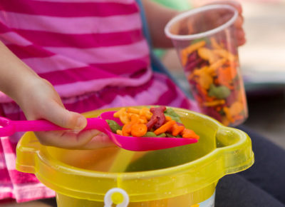 Young girl scoops goldfish crackers out of a bucket. She's putting the crackers into a cup.