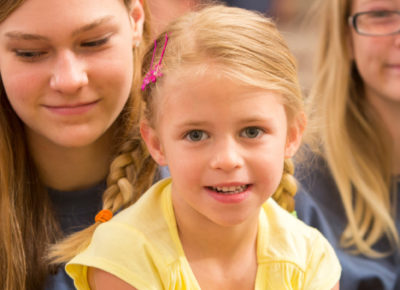 Little girl with blonde hair and pigtails stares directly at the camera and has a smirk on her face. She is sitting on a volunteers lap.