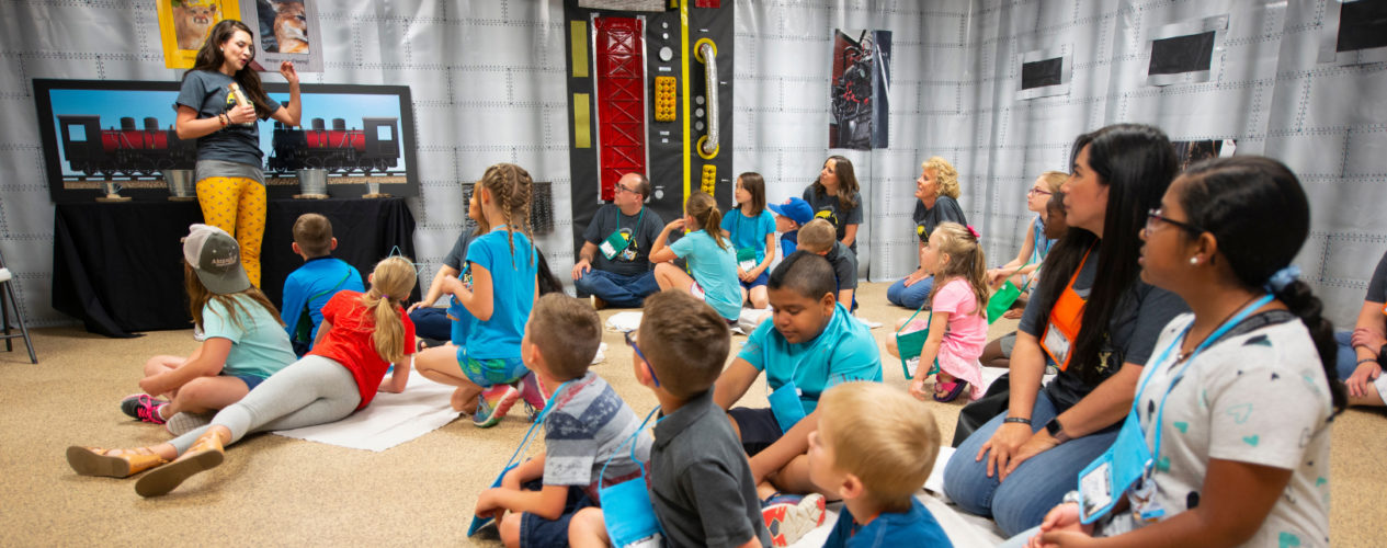 A group of children and volunteers gather in a children's ministry classroom.
