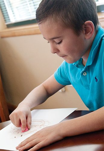 Elementary-aged boy erasing a page that is colored on with brown crayon.