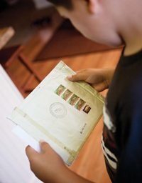A children looking at an envelope for a missionary he supports.