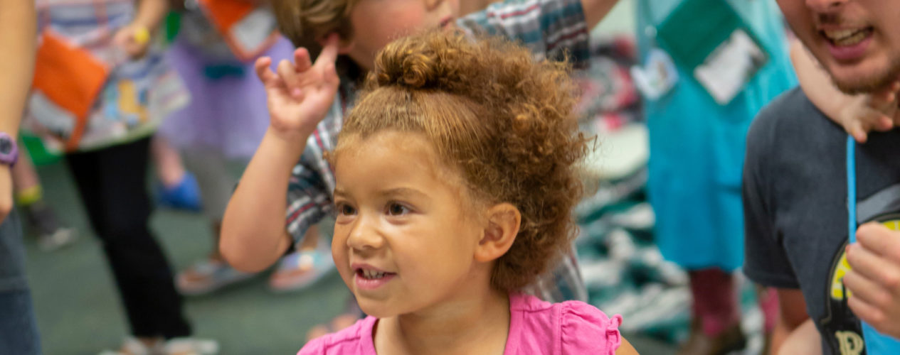 A toddler dances to music in her classroom.