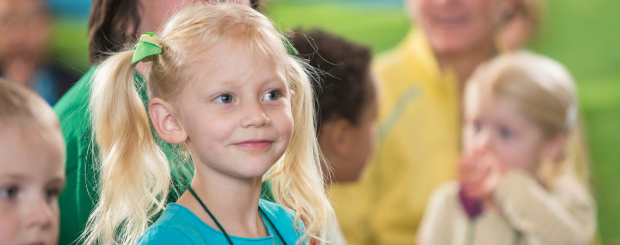 An elementary girl smiles as she listens to the lesson.