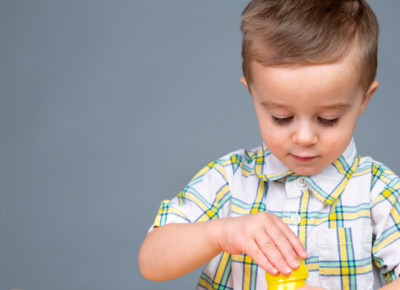 A preschool boy stacks parts of plastic Easter eggs.