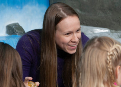 A female children's ministry volunteer is leading a small group of children.