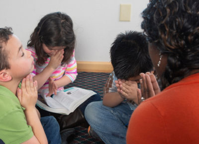 A group of elementary kids praying during a lesson.