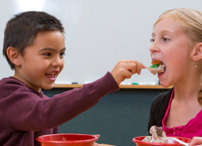 Two elementary kids are eating ice cream.