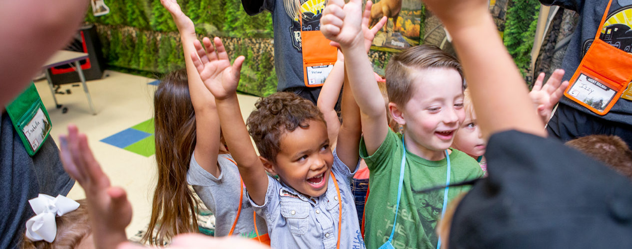 A group of preschoolers with their hands up in celebration.
