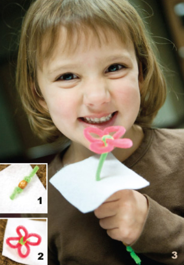 "Little girl holding her ""Faith Like a Seed"" craft. In one corner there is a insert that shows the wooden bead wrapped in a green chenille wire. The other part of the corner shows the flowers made of chenille wire."