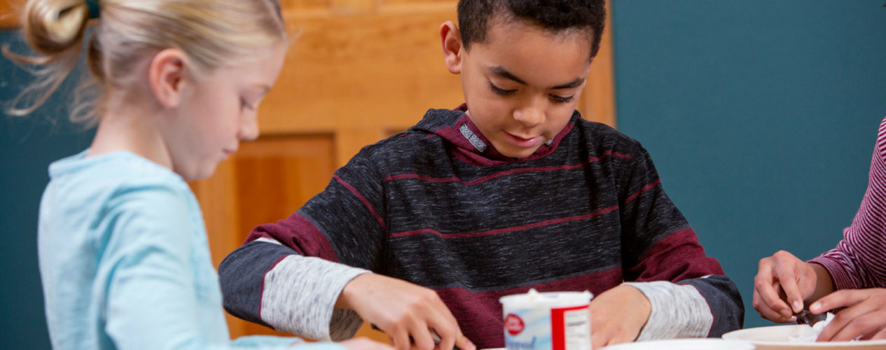 Two elementary aged kids are sitting at a table, frosting cookies.