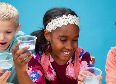 Three elementary kids are sitting at a table with a blue backdrop behind them They are each holding a clear plastic cup with a liquid that's fizzing.