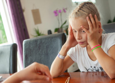 An older girl has her head in a hands as she looks on confused by an object lesson.