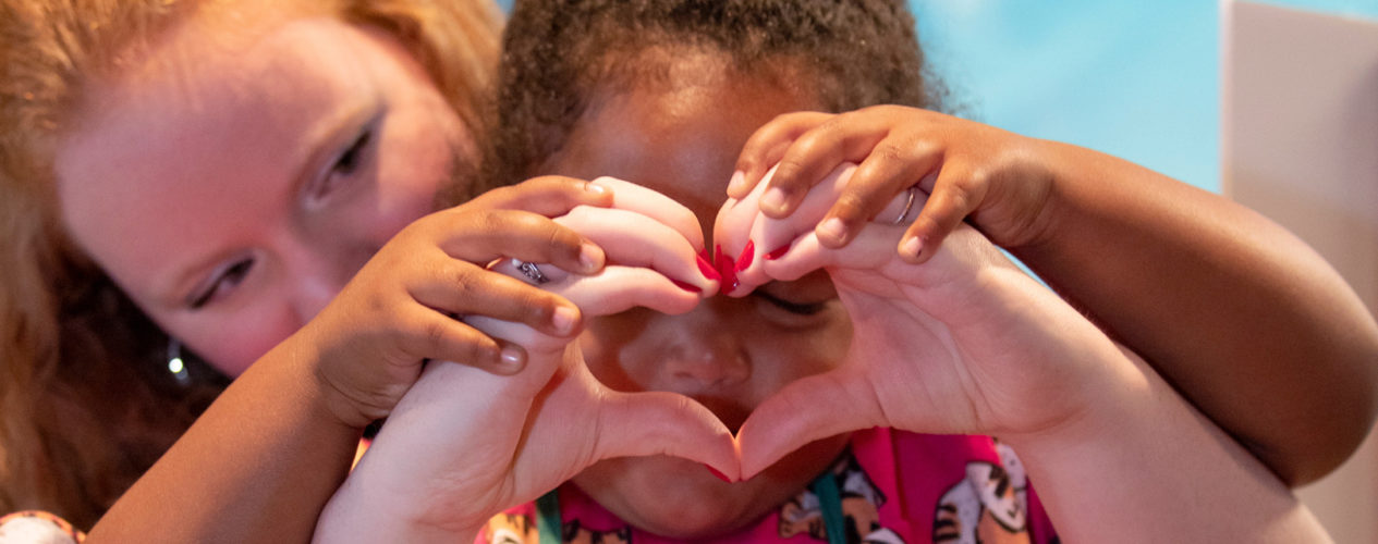 An woman volunteer makes a heart with her hands as a young girl holds the hands to her face and places her hands on top of the volunteer's hands.