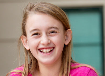 Preteen girl in a pink shirt smiles at the camera.