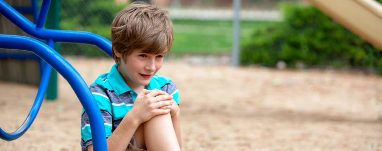 An elementary-aged boy sitting on the ground of the playground. He looks very upset.