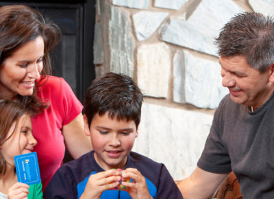 A family with a mom, dad, son and daughter are sitting in front of a fireplace playing a game.