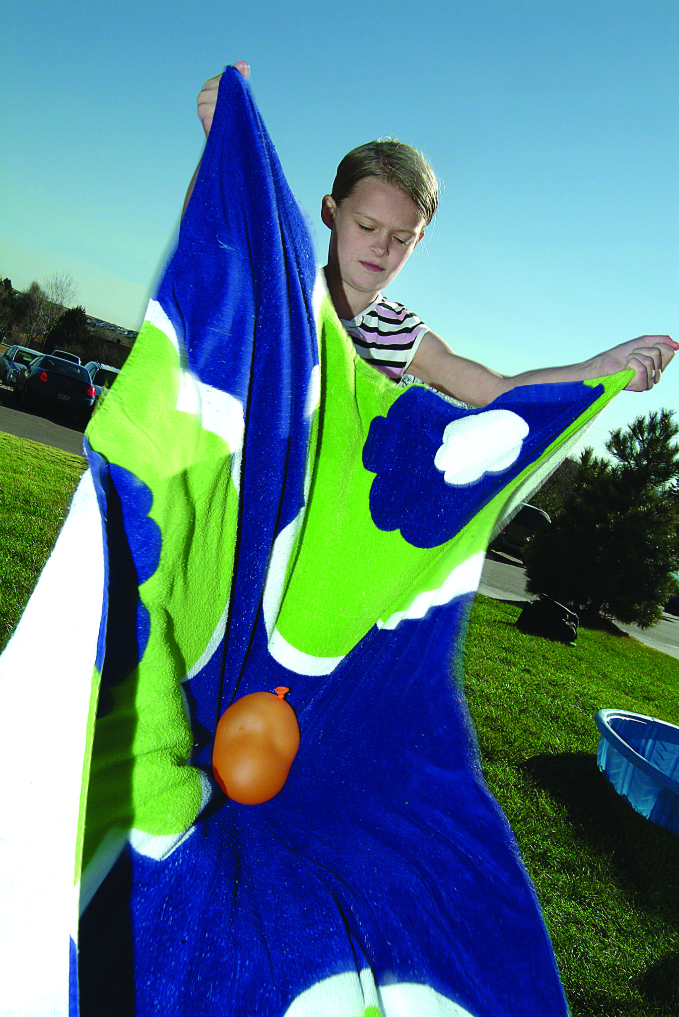 A boy tosses a water balloon with a blanket.