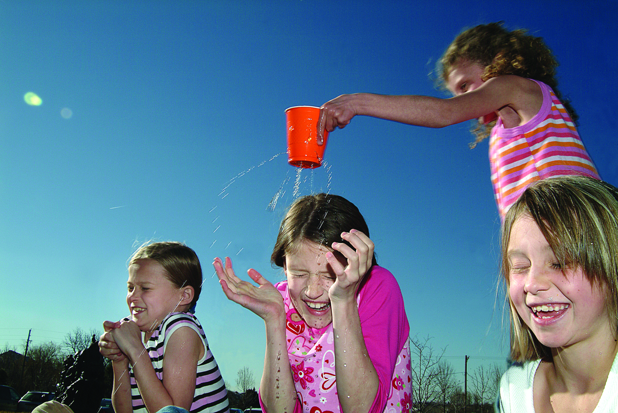 A child with a leaky cup walks around sprinkling friends with water.