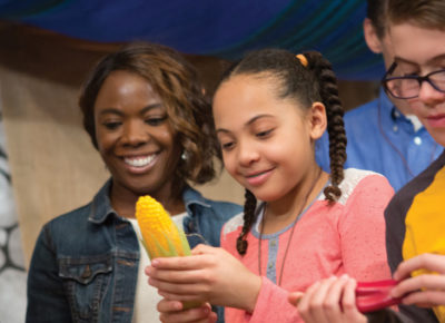 Preteen girl holding a plastic ear of corn as her peers grab other plastic food. Their teachers look on smiling.