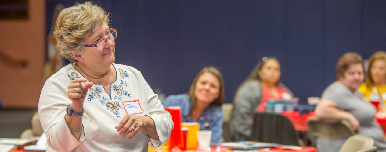 A older woman volunteer stands up and talks during a teacher training meeting.