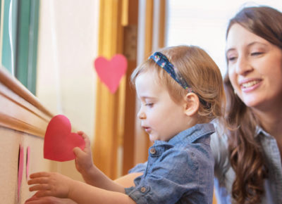 A mom is helping her toddler decorate with hearts.