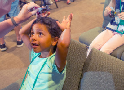An elementary aged girl puts her hands on her head and smiles as a children's ministry volunteer talks to her about fear.