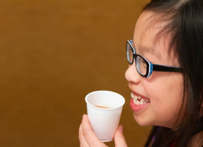 An elementary aged girl drinks out of a paper cup.