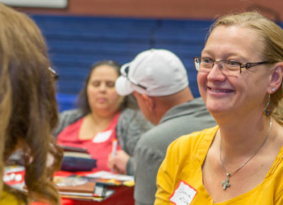 A female volunteer smiles at a volunteer recruiting event.