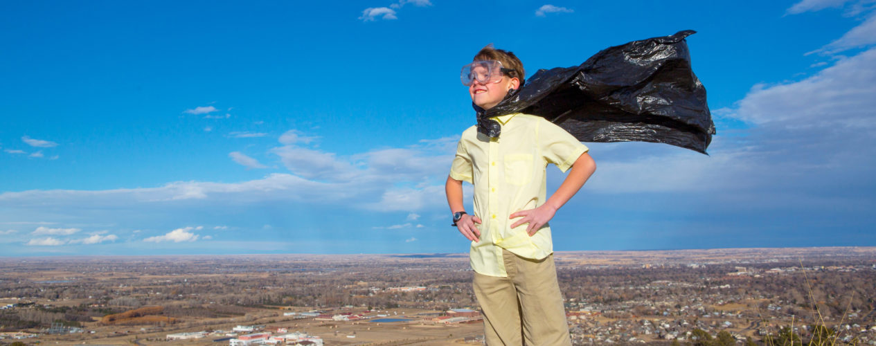 A child standing on a hill with a black superhero cape blowing int he wind.