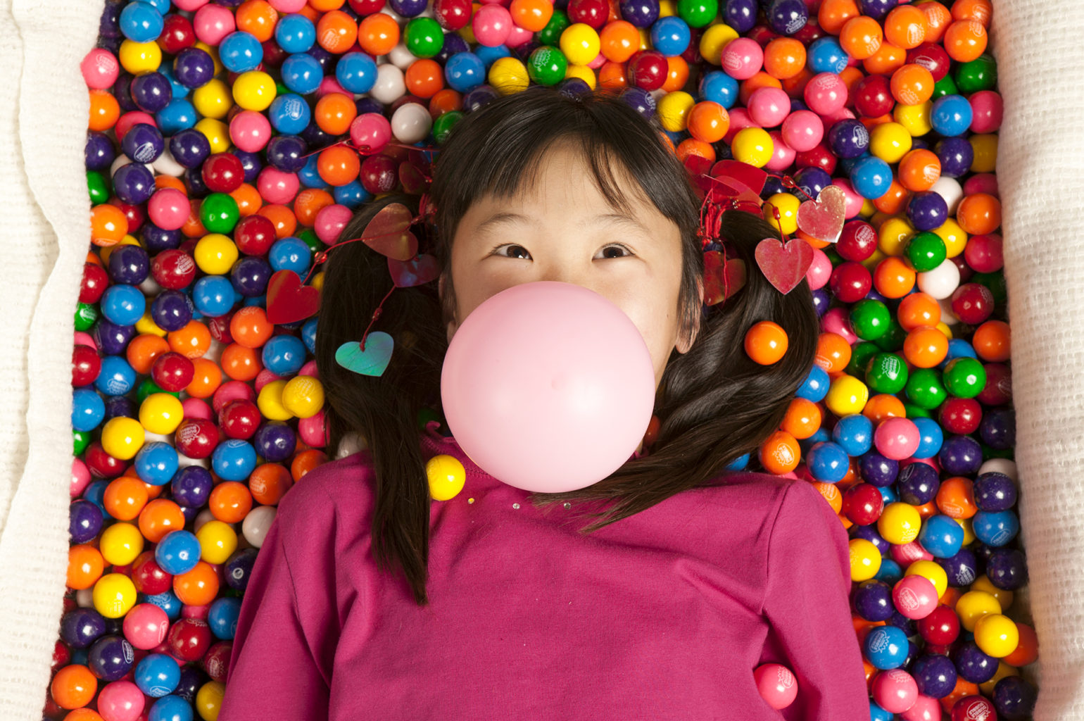 A girl is laying on top of a pile of gum balls. She's blowing a bubble out of chewing gum.