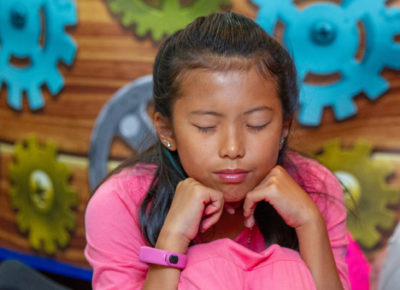 A preteen girl has her eyes closed in deep prayer.
