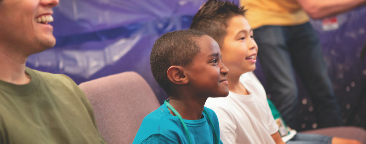 Two preteen boys are sitting in the sanctuary chairs next to their adult leader.