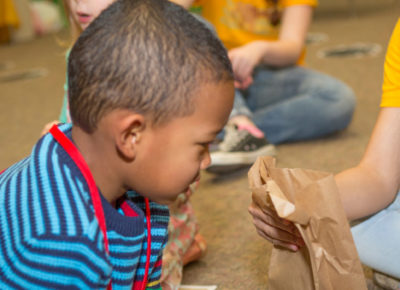 A preschool boy looks inside a brown paper bag.