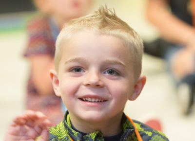 A preschool boy smiles during a Bible story.