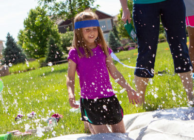 Little girl sliding down a slip and slide as other kids dump water on her.