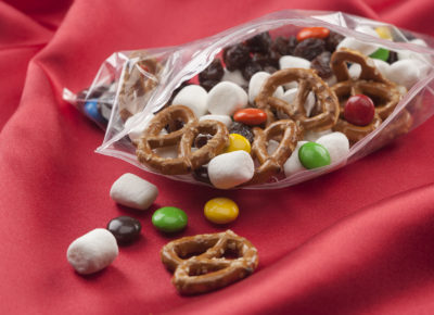 A bag of travel mix featuring mini marshmallows, pretzels and M&Ms is sitting on a red table cloth.