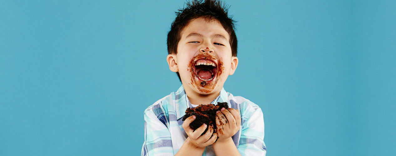 Boy, standing in front of a bright blue background, excitedly has a huge chunk of cake in his hand. His smile is covered in frosting.